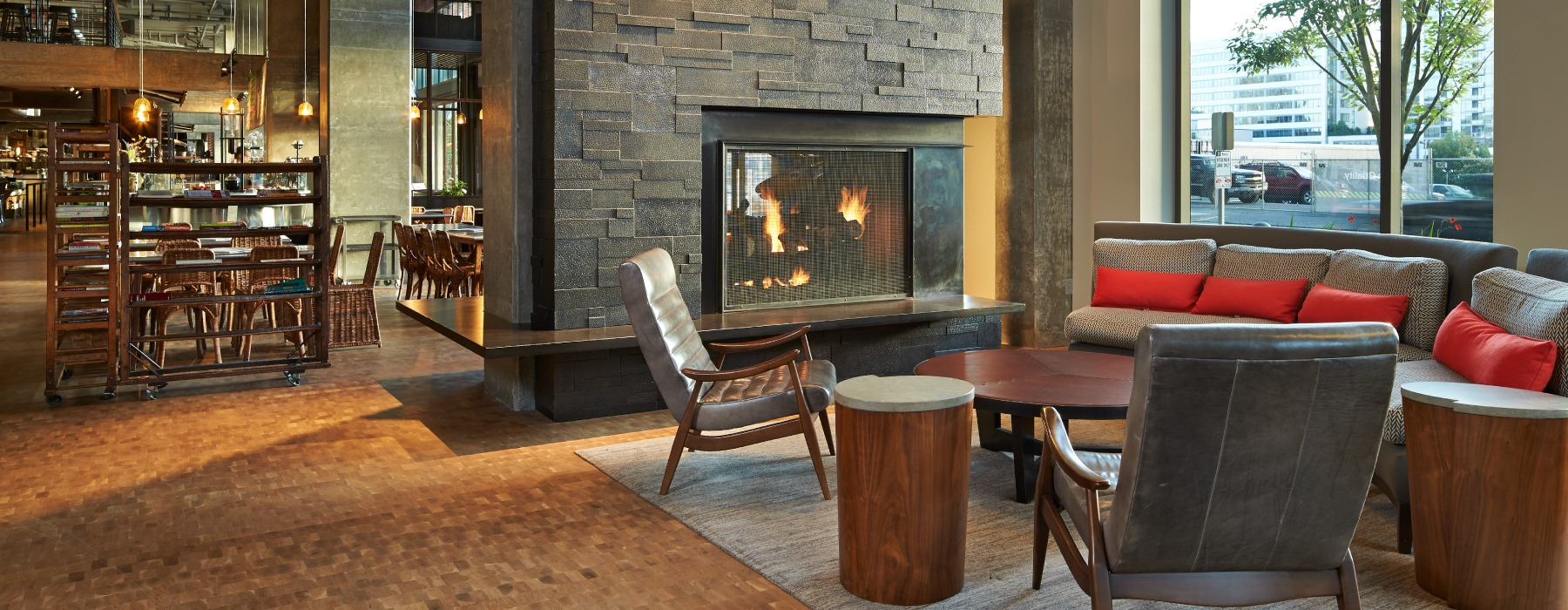 Lobby with plush seating and fireplace, large window for view passers by and plenty of natural lighting
